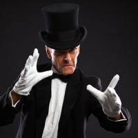 Magician making mysterious gestures. Wearing black suit and hat. Studio shot against black.